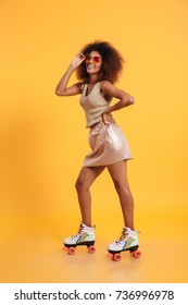 Full length portrait of a happy afro american woman dressed in retro clothes and wearing skates while standing and posing isolated over yellow background
