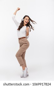 Full length portrait of a happy asian businesswoman listening to music with headphones while dancing isolated over white background