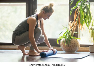 Full length portrait of happy attractive young woman folding blue yoga or fitness mat after working out at home in living room. Healthy life, keep fit concepts. Horizontal image