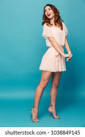Full length portrait of a happy beautiful girl wearing dress posing while standing isolated over blue background