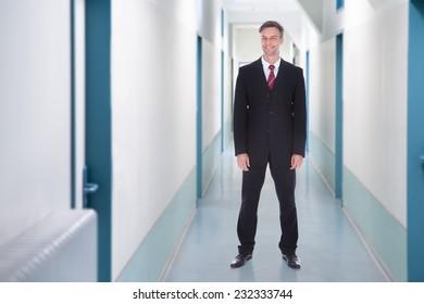 Full length portrait of happy businessman standing in office corridor
