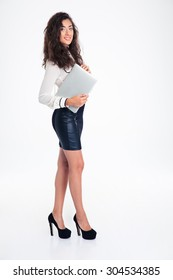 Full length portrait of a happy businesswoman standing with laptop isolated on a white background