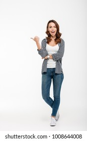 Full length portrait of a happy casual girl winking and pointing finger away isolated over white background