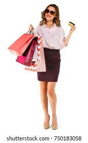 Full length portrait of happy casual woman wearing sunglasses, standing and holding colorful shopping bags and gold credit card isolated on a white isolated background. Shopping concept