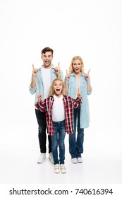 Full length portrait of a happy cheerful young family with a child standing together and pointing fingers up at copy space isolated over white background