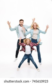 Full length portrait of a happy cheerful family with a child jumping together with outstretched hands isolated over white background