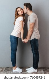 Full length portrait of a happy cheery couple holding hands and kissing over gray wall