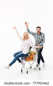 Full length portrait of a happy couple having fun with a supermarket trolley and waving isolated over white background