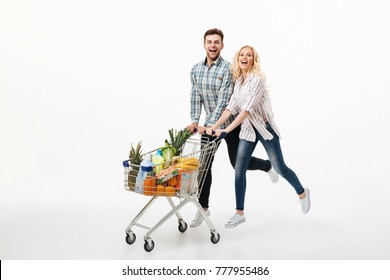 Full length portrait of a happy couple running with a supermarket trolley isolated over white background