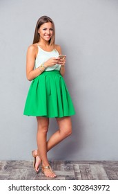 Full length portrait of a happy cute girl using smartphone on gray background and looking at camera