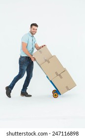 Full length portrait of happy delivery man pushing trolley of boxes on white background
