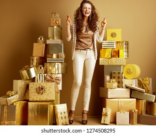 Full length portrait of happy elegant fashion-monger in gold beige clothes with crossed fingers among 2 piles of golden gifts in front of a plain wall. birthday or deals, sales, discounts illustration