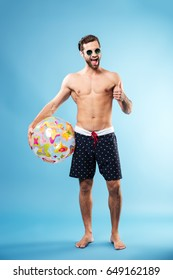 Full length portrait of a happy excited guy holding beach ball and showing thumbs up gesture isolated over blue