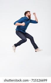 Full length portrait of a happy excited bearded man jumping and shouting isolated over white background