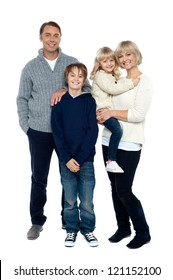 Full length portrait of a happy family posing in trendy winter wear outfits.