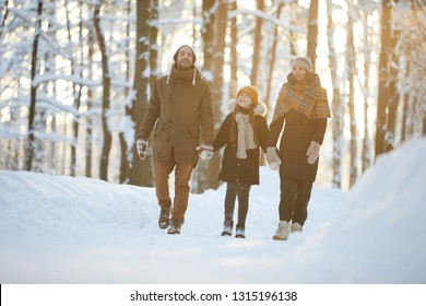 Full length portrait of happy family holding hands enjoying walk in winter forest lit by sunlight, copy space