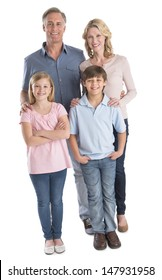 Full length portrait of happy family of four smiling against white background