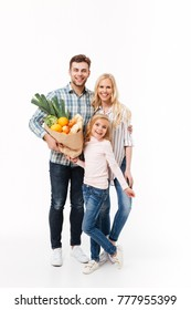 Full length portrait of a happy family holding paper shopping bag full of groceries while standing and looking at camera isolated over white background