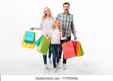 Full length portrait of a happy family holding paper shopping bags while walking isolated over white background