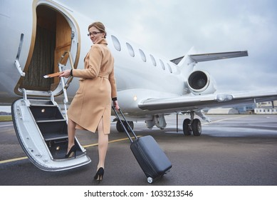 Full length portrait of happy female holding cards and baggage while going upstairs. Journey concept