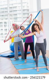 Full length portrait of happy female friends exercising with resistance bands in gym