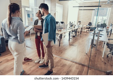 Full length portrait of happy four coworkers talking in workroom with glass wall on background. Copy space in right side