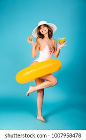 Full length portrait of a happy girl dressed in swimsuit posing with inflatable ring while standing and holding cocktail isolated over blue background