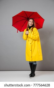 Full length portrait of a happy girl dressed in raincoat and rubber boots posing while standing with an open umbrella isolated over gray background