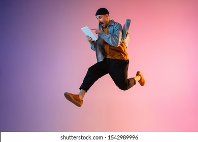 Full length portrait of happy jumping man wearing casual clothes in neon light isolated on gradient background. Emotions, ad concept. Using tablet, hurrying up, late for work or sale, shopping.