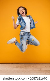 Full length portrait of a happy little schoolgirl jumping over yellow background