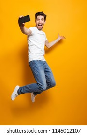 Full length portrait of happy man with brown hair jumping and screaming while taking selfie on black smartphone isolated over yellow background