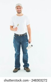 Full length portrait of happy man holding paint roller and paintbrush on white background