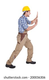 Full length portrait of happy manual worker pushing billboard over white background