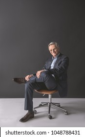 Full length portrait of happy mature male sitting on comfortable seat. Glad resting employer concept