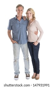 Full length portrait of happy mature couple standing with hands in pockets over white background