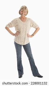 Full length portrait of happy mature woman in casuals with hands on hip over white background