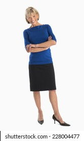 Full length portrait of happy mature businesswoman standing arms crossed over white background