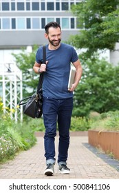Full length portrait of happy mature man walking outdoors with handbag and laptop