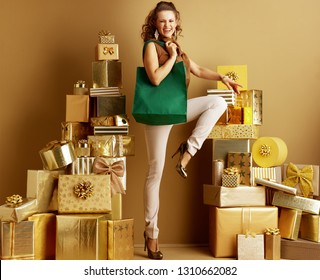 Full length portrait of happy modern shopper woman in gold beige pants and brown blouse with eco friendly green bag among 2 piles of golden gifts in front of plain wall. Environment friendly shopper.