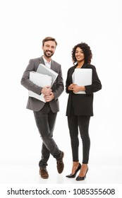 Full length portrait of a happy multiracial business couple holding folders isolated over white background