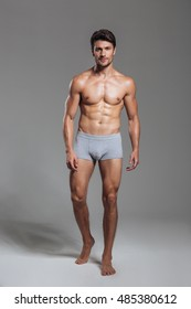 Full length portrait of a happy muscular man in underwear standing isolated on a gray background
