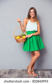 Full length portrait of a happy pretty girl holding basket with fruits over gray background