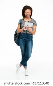 Full length portrait of a happy pretty teenage girl wearing backpack and using pc tablet isolated over white background
