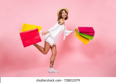 Full length portrait of a happy pretty girl holding shopping bags while running and looking at camera isolated over pink background