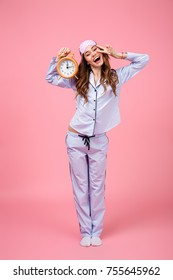 Full length portrait of a happy pretty girl dressed in pajamas holding alarm clock while standing and showing peace gesture isolated over pink background