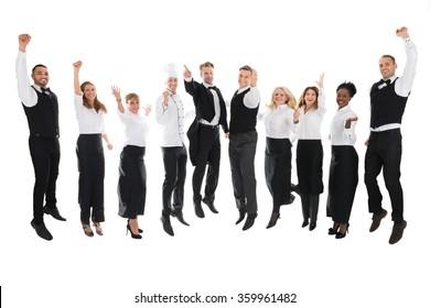 Full length portrait of happy restaurant staff celebrating success against white background
