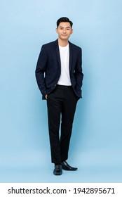 Ganzes Portrait von glücklich lächelndem jungen, gut aussehenden südostasiatischen Geschäftsmann auf hellblauem Studiohintergrund