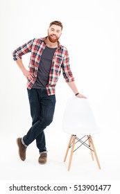 Full length portrait of a happy smiling casual man standing and leaning on chair with hand over white background