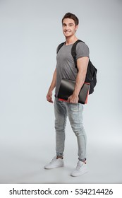 Full length portrait of a happy smiling student standing with backpack and folders over white background