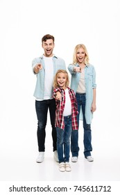 Full length portrait of a happy smiling family with a child standing together and pointing fingers at camera isolated over white background